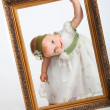 Stock Photo: Portrait of girl with frame. Little funny girl looking through fr