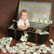 Stock Photo: Cute little boy іs sitting in suitcase with money
