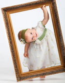 Portrait of a girl with the frame. Little funny girl looking through the fr — Stock Photo