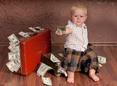 The boy is sitting on a suitcase with the money and handed the money — Stock Photo