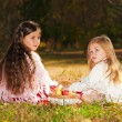 Two girls read the book while sitting on the grass. — Stock Photo