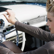 Постер, плакат: Beautiful girl blond with visage and hair up sits in the old car