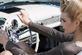 Beautiful girl, blond with visage and hair-up, sits in the old car. — Stock Photo