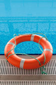 Lifebuoy in blue water in swimming pool — Stock Photo