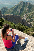 Woman sits on rocky and photographs — Stock Photo