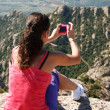 Girl on edge and photographs a landscape — Stock Photo
