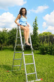 Woman on a ladder in garden — Stock Photo