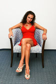 Sexy woman in red dress in chair — Stock Photo