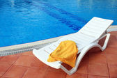 Relax chair near the pool with towel — Stock Photo