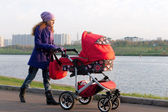 Mother with a baby carriage — Stock Photo