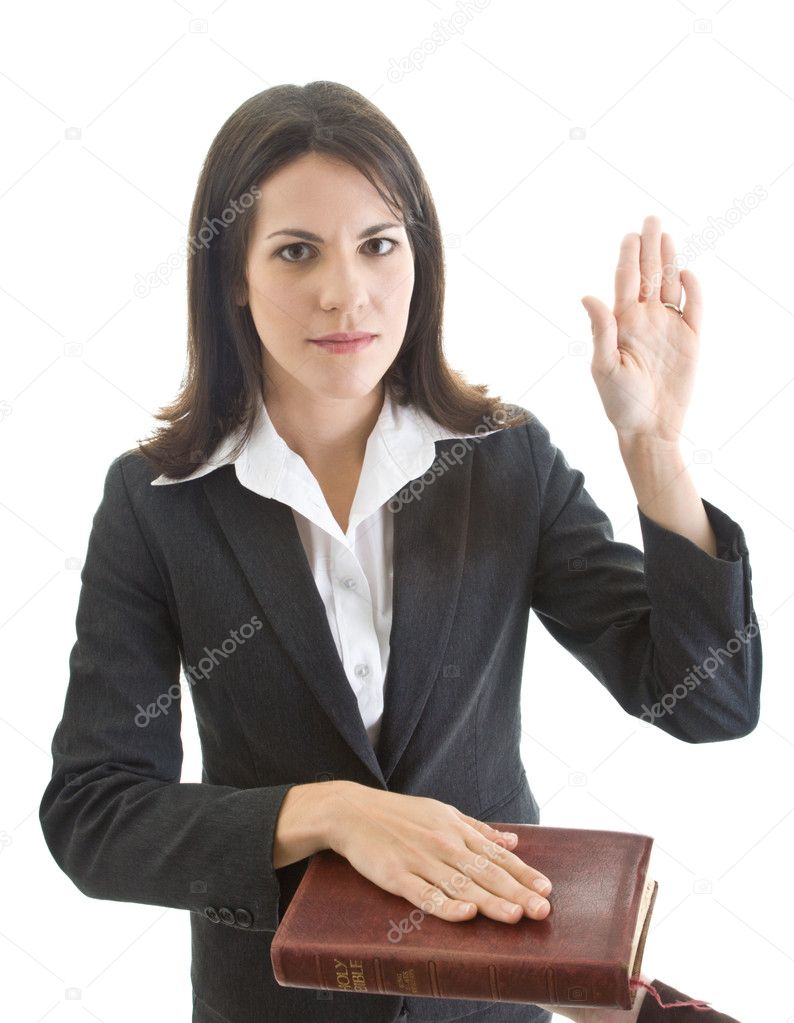 Caucasian woman looking at camera and swearing on a bible.  Isolated on white.  Stock Photo #7811605