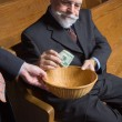 Senior Man Putting Money into Church Basket - Stock Photo
