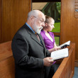 Stock Photo: Older Man Young Woman Standing in Church Singing Holding Hymnals
