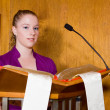 Stock Photo: Young CaucasiWomReading from Bible at Church Lectern