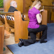 Young Woman Genuflecting Sign Cross Church Pew - Stock Photo