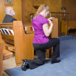 Stock Photo: CaucasiWomKneeling Crossing Herself Church