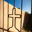 Cross Shape Iron Gate Adobe Wall Blue Sky Vignette - Stock Photo