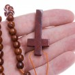 Hand Holding a Wooden Rosary Cross Isolated — Stock Photo