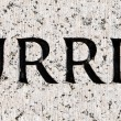 "Word ""Hurried"" Carved in Gray Granite Stone - Stock Photo"