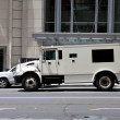 Side View Armoured Armored Car Parked on Street Outside Building - Stock Photo