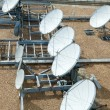 Stock Photo: Collection of Large Satellite Dishes on Flat Gravel Roof