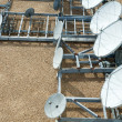 Collection of Large Satellite Dishes on Flat Gravel Roof — Stock Photo