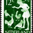 Stock Photo: Canceled Dutch Netherlands Postage Stamp Farm Girl Feeding Chick