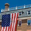 Colonial Revival Style Building with Large American Flag Blue Sk - Stock Photo