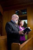Alter Mann junge Frau Kirche singen Gesangbücher — Stockfoto