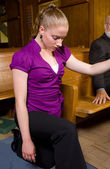 Young White Woman Genuflecting Next to Church Pew — Stock Photo
