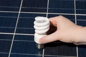 Hand Compact Fluorescent Light Bulbs Solar Panel — Stock Photo