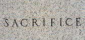 "Word ""Sacrifice"" Carved in Gray Granite Stone — Stock Photo"