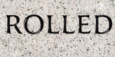 "Word ""Rolled"" Carved in Gray Granite Stone — Stock Photo"