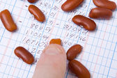 Finger Tip Kidney Beans on Ledger Book Accounting — Stock Photo