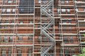 Andamios en proceso de renovación del edificio del ladrillo antiguo — Foto de Stock