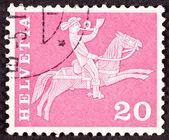 Schweiziskt frimärke ridning postutdelning, rider blåser posta — Stockfoto