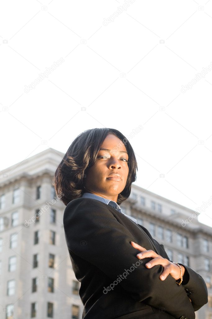 Tough-Looking African American businesswoman with serious expression looking at camera.  Shot outdoors with office building and blown out sky. — Stock Photo #7893069