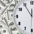 Clock with hand on money background — Stock Photo