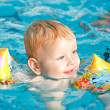 Little boy floating in pool - Stock Photo