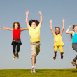Group of four kids jumping — Stock Photo