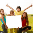 Group of multi ethnic children holding a white board — Stock fotografie