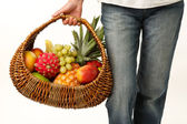 Wicker basket with fruits in female hand — ストック写真