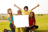 Group of multi ethnic children holding a white board — Stockfoto