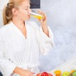 Young woman drinking fresh juice in kitchen — Stock Photo #7789941
