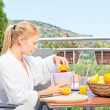 Woman making morning juice on terrace — Stock Photo