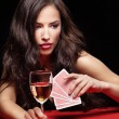 Stock Photo: Pretty woman gambling on red table
