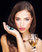 Pretty young woman holding dices on black background — Stock Photo