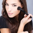 Young pretty girl doing makeup with powder brush — Stock Photo
