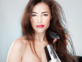 Woman with long hair holding blow dryer — Stock Photo