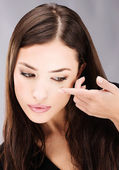 Woman holding contact lens on finger in front of her eye — Stock Photo